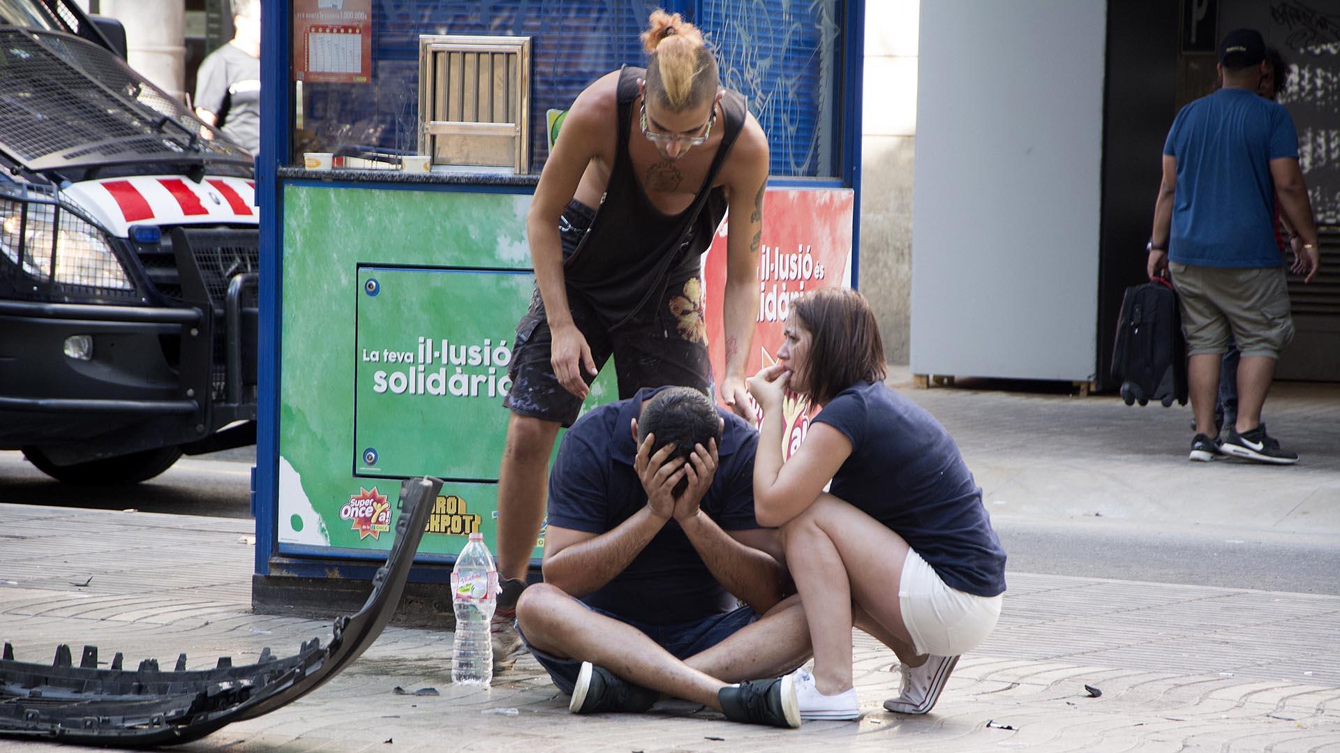 GRA180. BARCELONA, 17/08/2017.- Varios jóvenes permanecen junto a los restos de un vehículo, en el lugar del atropello masivo realizado por una furgoneta que ha arrollado esta tarde a varias personas que paseaban por las Ramblas de Barcelona. Los Mossos d'Esquadra y los equipos de emergencias sanitarias han desplegado un amplio dispositivo en esta zona, en el centro turístico de la capital catalana, frecuentada a diario por miles de turistas, que ha quedado acordonada. EFE/David Armengou