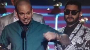 Residente de frente al micrófono y con el Grammy, atrás, Trooko