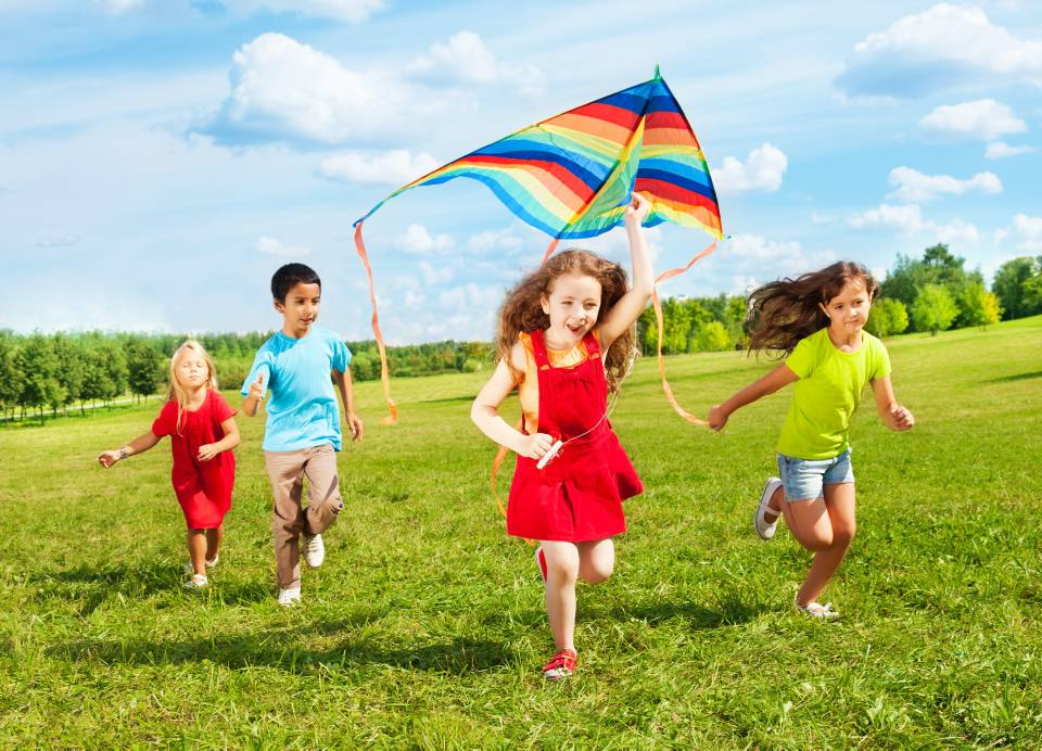 Group of four kids running in the park with kite happy and smiling on summer sunny day